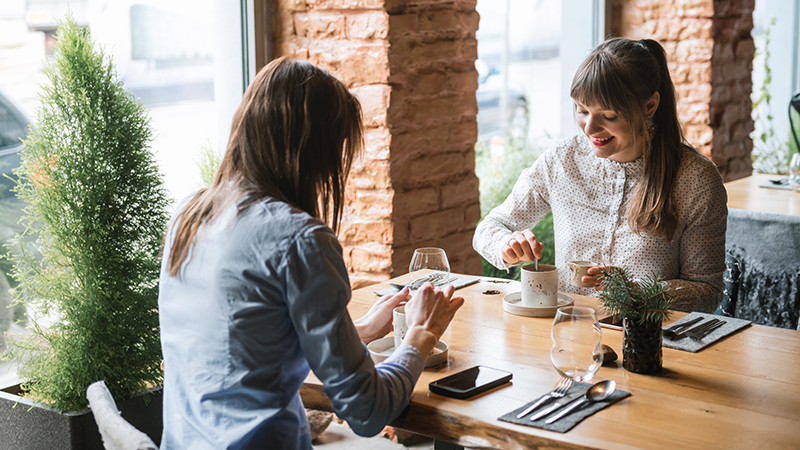 Young women meeting in cafeteria and drinking coffee at table in modern interior while chatting happily