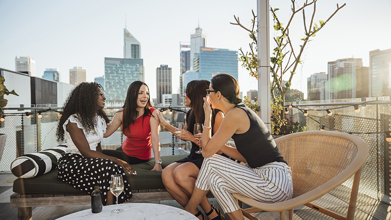 A group of businesswomen sitting on chairs on a Perth hotel rooftop having drinks and laughing together after work.